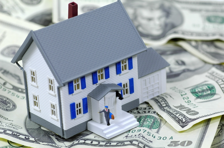 Investment property Insurance - toy house on dollar bills