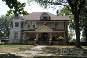 LOCKPORT, ILLINOIS / UNITED STATES - SEPTEMBER 6, 2015:  A large stucco and limestone block home in historic Lockport, Illinois.