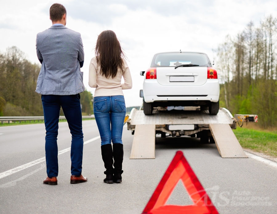 Couple near tow-truck picking up broken car. AIS Auto Insurance Specialists offers Roadside Assistance coverage.