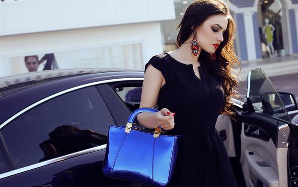 Woman with luxury handbag stands near luxury car_600x