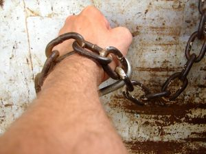 arm shackled to a wall with large chain