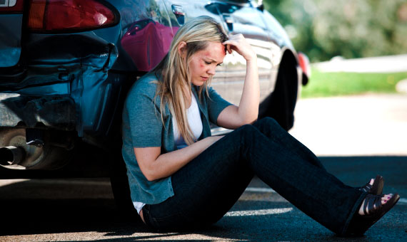 car insurance - car accident victim sitting on the ground